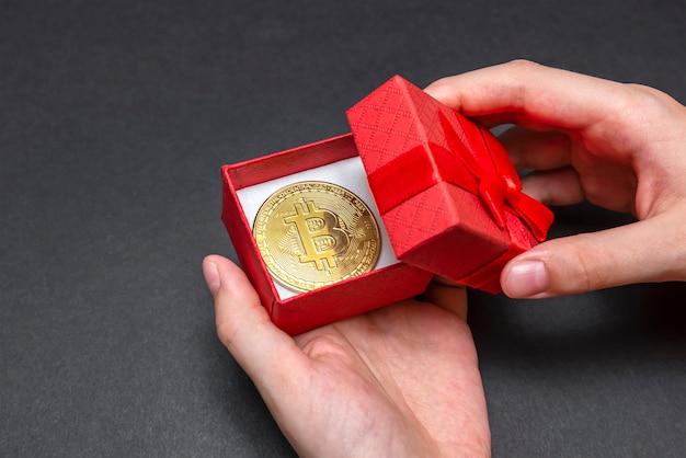 赤いギフトボックスに入ったビットコインコイン。クリスマスと新年の贈り物。手はビットコインコイン、バナーでギフトボックスを開きます。