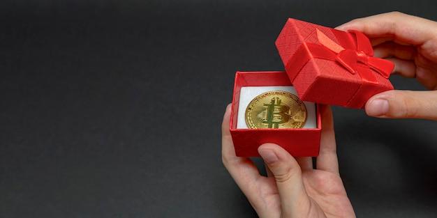 リングまたは暗号通貨ジュエリーのコンセプトのためのギフトボックス内のビットコインコイン、最高のギフト。クリスマスと新年の贈り物。手はビットコインコイン、バナーでギフトボックスを開きます。