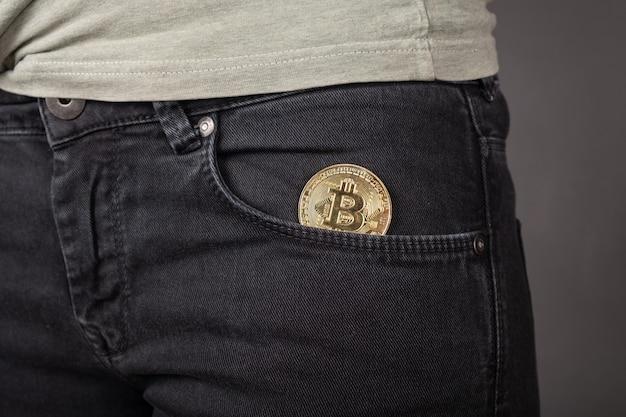 Биткойн монета в кармане брюк, скопление криптовалюты крупным планом