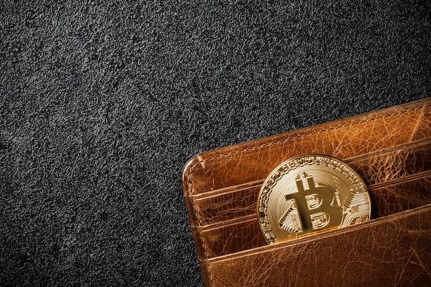 Монета биткойн в кошельке на черном фоне