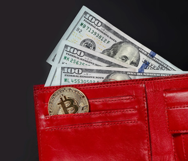Bitcoin coin and us dollars in red wallet on black , close up.