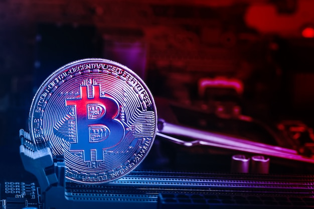 Bitcoin coin with abstract red glow motherboard and red blue lights.