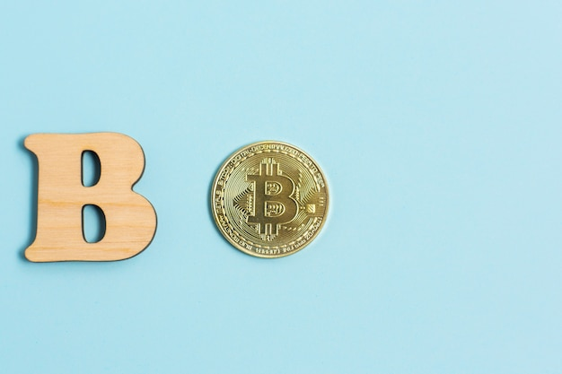 Bitcoin coin and next to wooden with b letter on blue surface