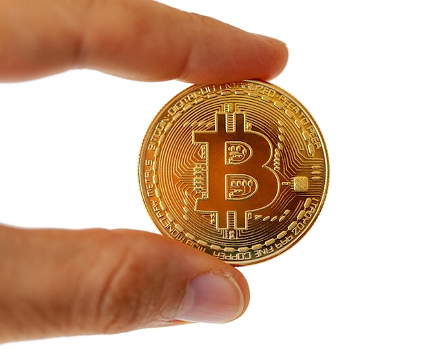 A bitcoin coin between your fingers. subject isolated on white wall.