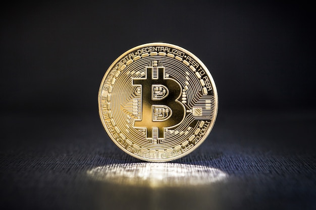 Bitcoin coins currency on a black  surface. the cryptocurrency bitcoin a mysterious light.