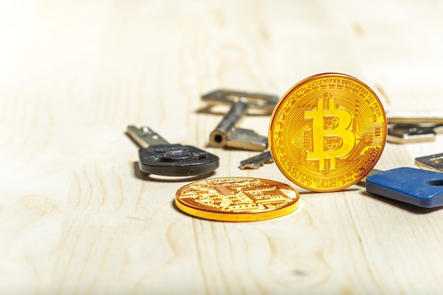 Bitcoin coins and key on wooden table