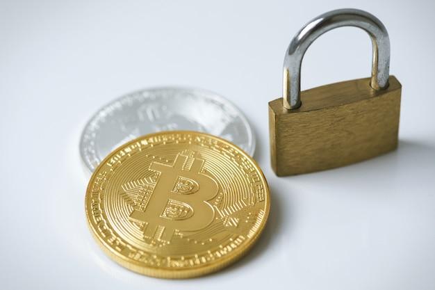 Bitcoin coins and padlock on gray