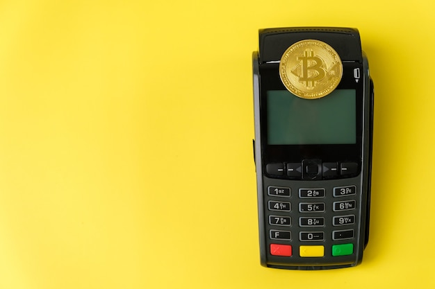 Bitcoin coins on the payment terminal on the yellow background