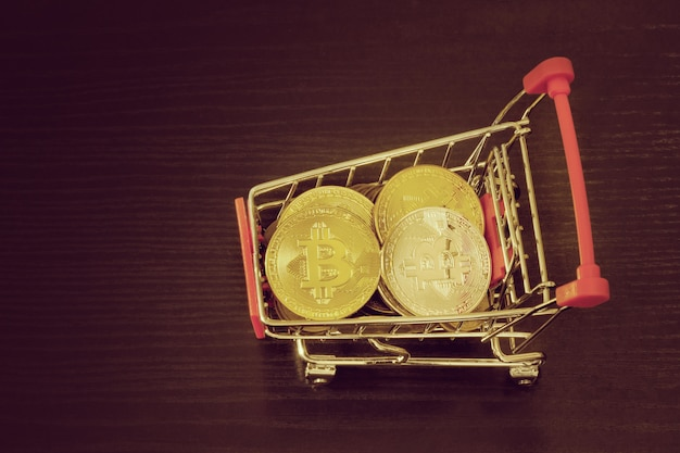 Bitcoin coins in shopping cart. black background. top view