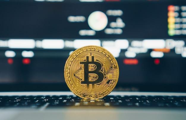 Биткойн криптовалюта цифровая реплика золотых денег монеты на ноутбуке с финансовыми торговыми акциями на экране. концепция финансирования бизнеса.