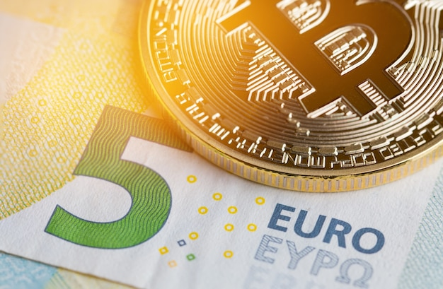 Bitcoin crypto currency is digital payment money, gold coins with on euro eyp5 bill