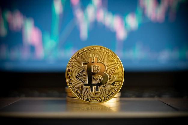 Монета криптовалюты bitcoin и финансовая диаграмма в фоновом режиме