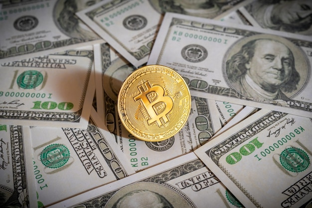 Bitcoin cryptocurrency coin and dollar bills in background