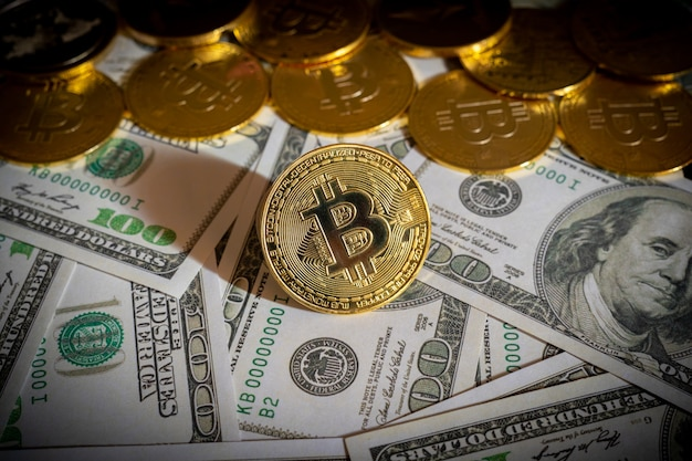 Bitcoin cryptocurrency coins and dollar bills in background