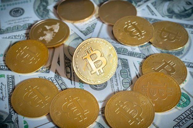 Bitcoin cryptocurrency coins and dollars bills in background