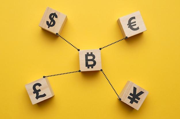 Концепция криптовалюты bitcoin и знаки валюты - абстрактные знаки на деревянных кубах с желтым космосом.