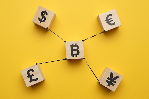 Bitcoin cryptocurrency concept and currency signs - abstract signs on wooden cubes with a yellow space.