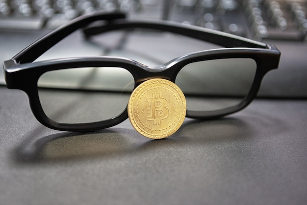 Bitcoin cryptocurrency concept.glasses and desktop keyboard at background. stock and exchange ocupation