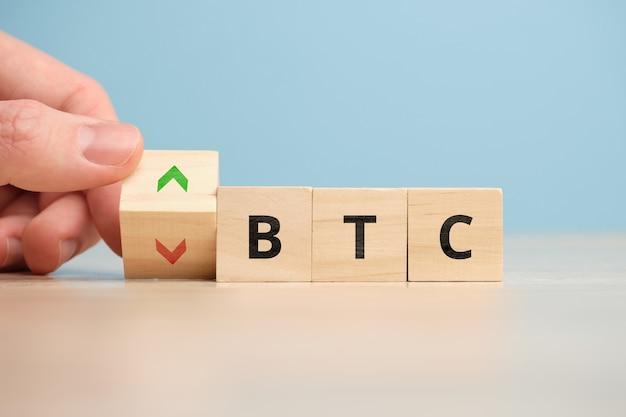 Концепция падения или роста криптовалюты bitcoin на деревянных кубиках.