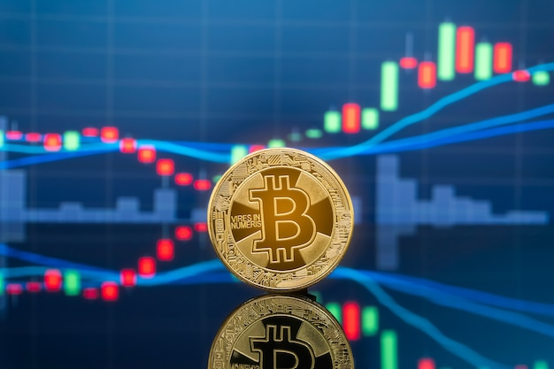 Bitcoin and cryptocurrency investing concept - physical metal bitcoin coins with global trading exchange market price chart in the background