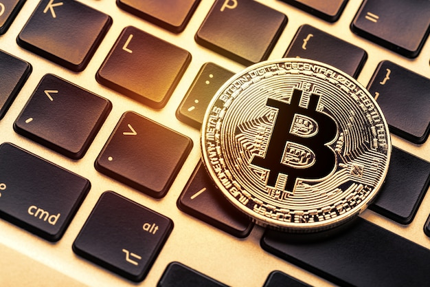 Bitcoin cryptocurrency on laptop keyboard.
