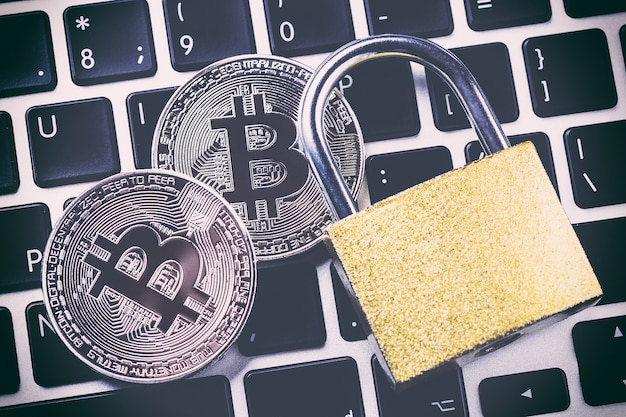 Bitcoin cryptocurrency with padlock on keyboard.