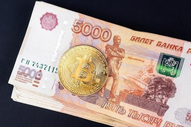 Биткойн криптовалюта с деньгами российских рублей, крупным планом пять тысяч банкнот