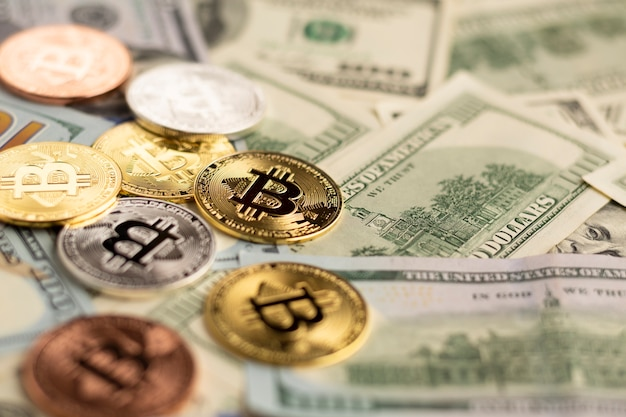 Bitcoin above dollar bills close-up