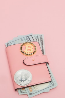Bitcoin and dollars in a pink wallet on the pink