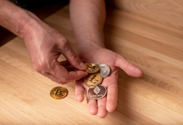 Bitcoin, etherium, eth, litecoin golden and silver coin in male hand. cryptocurrency and crypto investment.