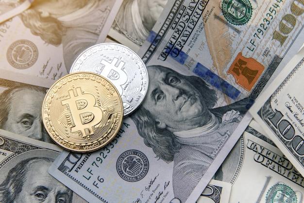 Биткойн золотые и серебряные монеты на банкнотах доллара сша. электронные деньги вложения. криптовалюта бизнес-концепция.