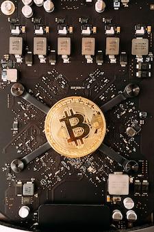 Золотая монета биткойн лежит на материнской плате компьютера