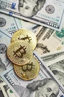 Золотые монеты bitcoin на долларовых купюрах сша