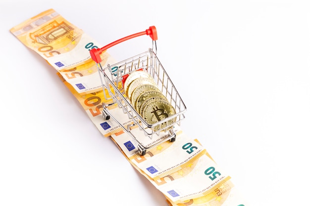 Bitcoin gold coins in the shopping cart on a few euro bills