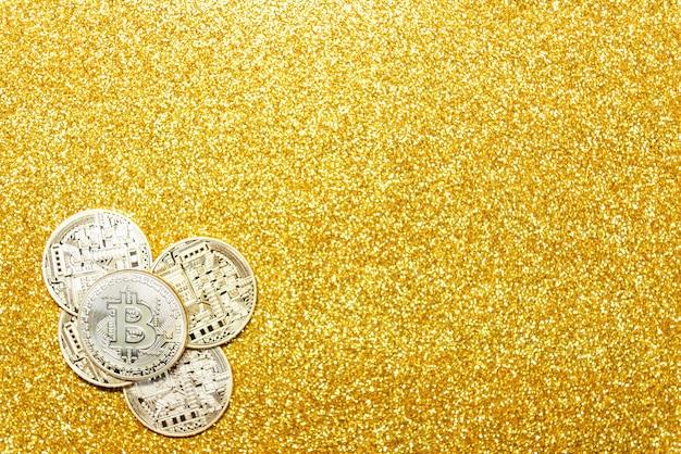 Bitcoin on gold glitter background.