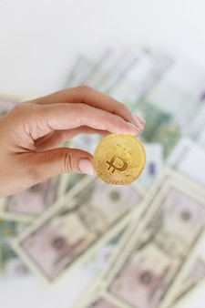 Bitcoin in hand against the background of money