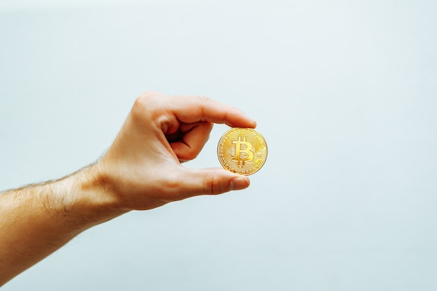 Bitcoin in hand on a light background high quality photo