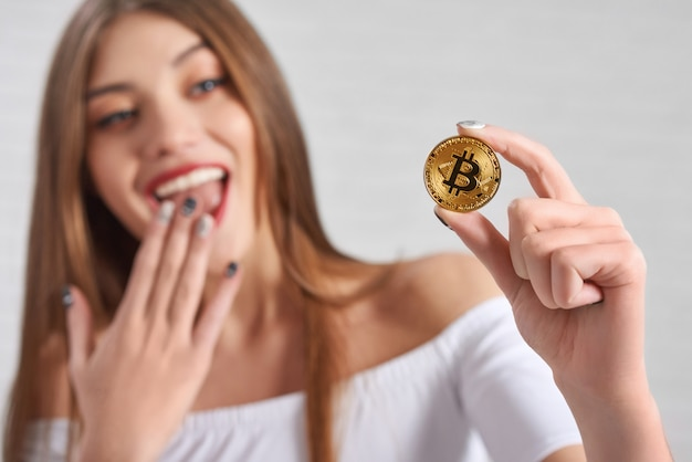 Bitcoin hold by excited pretty female model