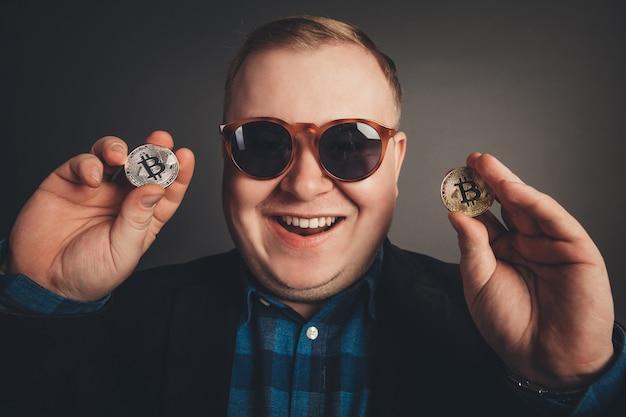 Биткойн в жирной руке бизнесмена, цифровой символ новой виртуальной валюты