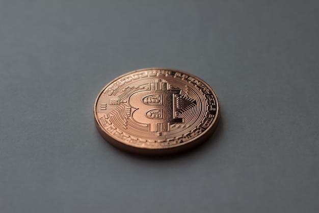 Bitcoin is placed on a gray background with shadow of a coin in low light