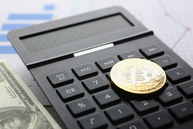 The bitcoin lies on keyboard of black calculator against graph financial statistics large.