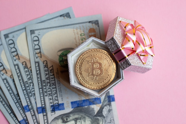 Bitcoin lies at small gift box on pink background.