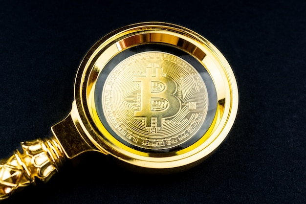 Bitcoin and magnifier black background