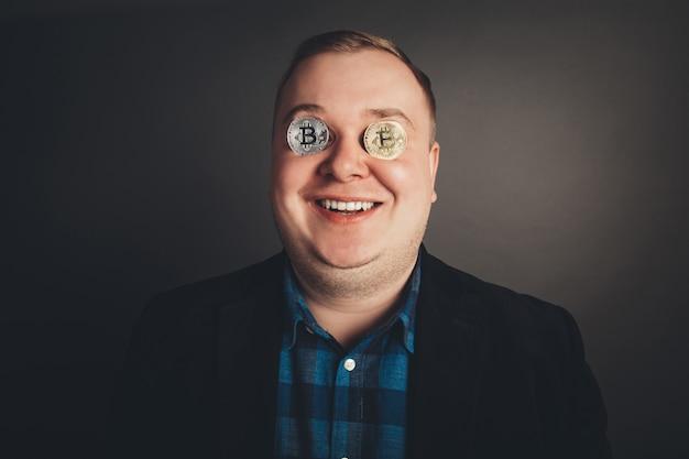 Любитель биткойнов с золотой монетой на глазах