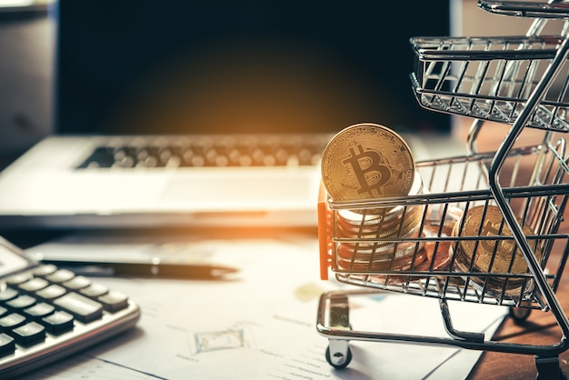 Bitcoin in mini shopping cart on table for work and laptop for work