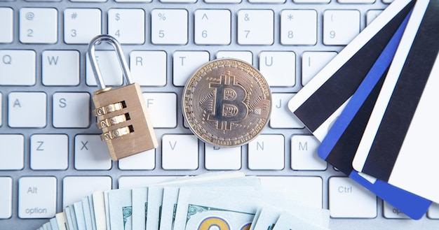 白いコンピューターのキーボードのビットコイン、お金、クレジットカード、南京錠。