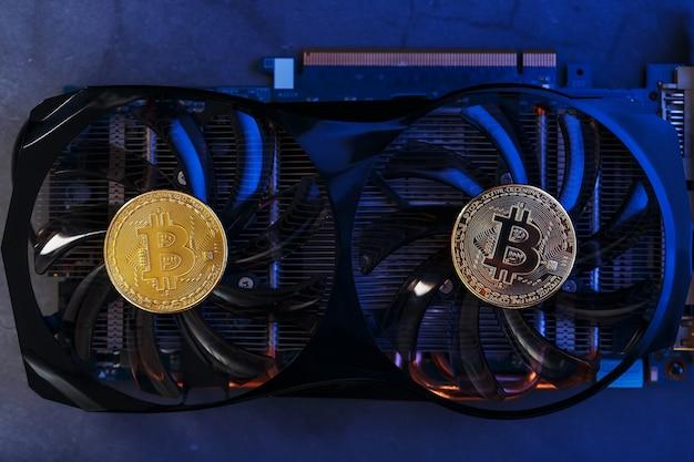 暗い背景に青いネオンライトが付いたグラフィックカードのビットコイン。暗号通貨マイニングの概念