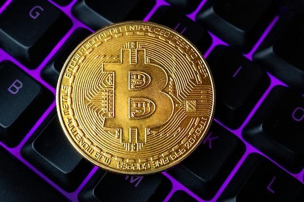 Биткойн на клавиатуре компьютера в фоновом режиме, символ электронных виртуальных денег и концепции добычи криптовалюты. монета криптовалюты биткойн лежит на клавиатуре. биткойн на клавиатуре.
