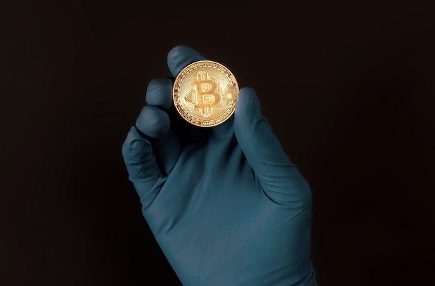 暗号通貨の兆候があるビットコインまたはbtcゴールデンコイン。保護手袋を手に