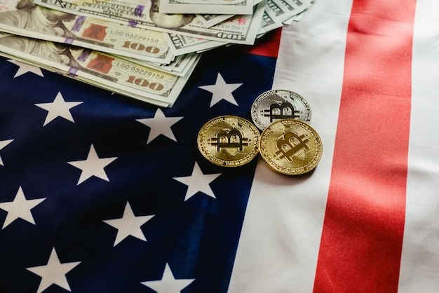 Bitcoin physical coins on american flag background with dollars in the background.